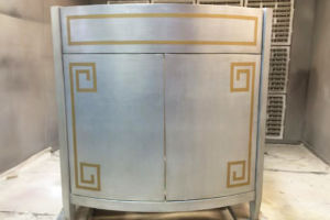 Bow front vanity finished in silverleaf and gold trim