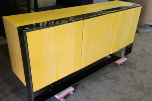 Yellow lacquered cerused four door cabinet with a chrome base